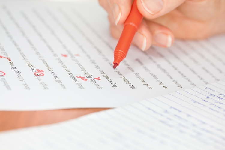 shutterstock_112331333 marking feedback Proofreader with red pen checks a transcribed page