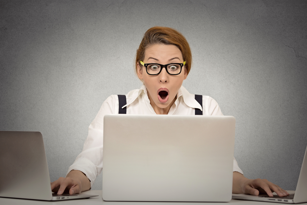 shutterstock_230977585 This is too much! Young woman can't handle workload anymore. Busy multitasking trying to manage it all by herself working on several computers simultaneously sitting at desk in office. Face expression