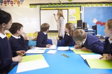 shutterstock_284502308 Pupils Sitting At Table As Teacher Stands By Whiteboard