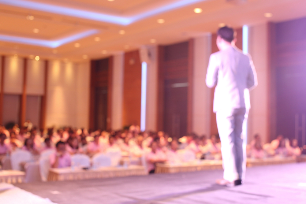 shutterstock_285658355 blurred image of businessman giving a speech on the stage
